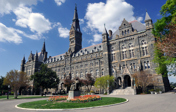 Washington, D.C., USA - April 9, 2012. Healy Hall with the statue of Georgetown University founder John Carroll in front and some people walking in background. Georgetown University is a top-ranking private university in the United States. It is located in the historic district of Georgetown in Northwest Washington, D.C.